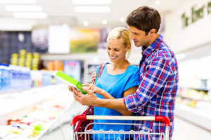 Couple Smiling While Reading Product Nutrition Label In Supermarket