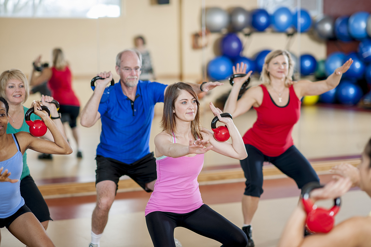 A group of adults are lifting weights during an aerobic fitness class at the gym.
