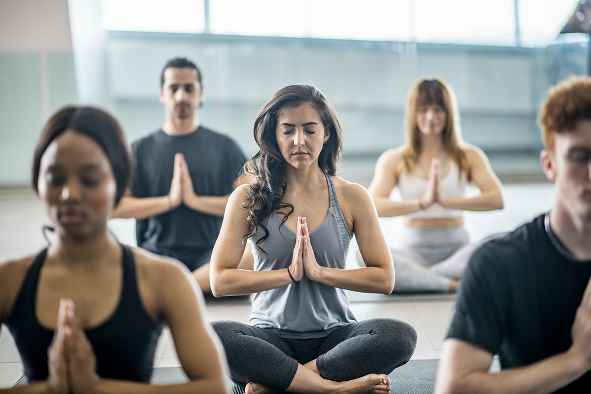 A group of people meditating in workout clothes.