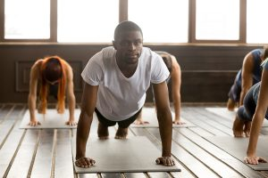 A young man and others practice yoga on mats.