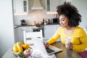 A young woman smiles as she looks at a laptop computer in her kitchen