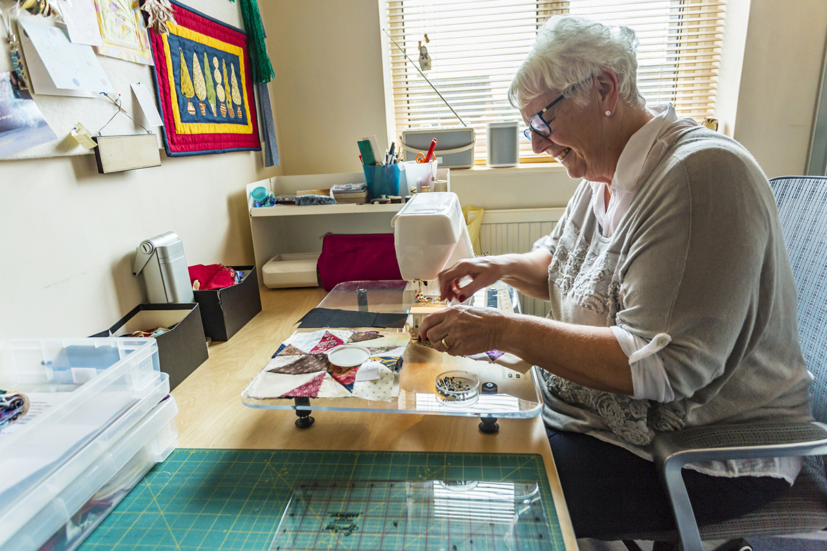 Active senior woman sewing in her home sewing room