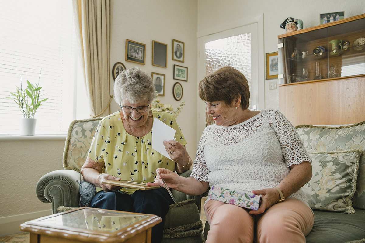 Two senior women are sitting at home together looking at old photographs and photo albums.