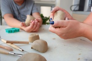 Hands of mother and son shaping clay